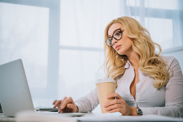 beautiful businesswoman working at laptop in office and holding coffee in paper cup