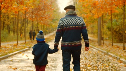 Little boy and his grandfather are walking in the autumn park