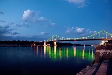 Night landscape. The city of Kiev, Ukraine, Europe. Pedestrian bridge across the Dnieper River. Wide angle