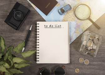 world map for to do list planning vacation with other travel accessories around.