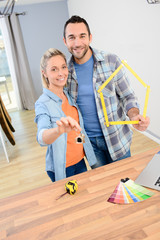 cheerful young couple making future project by renovating their new home and holding their house keys
