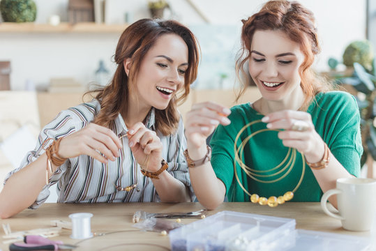 happy excited women making accessories in workshop