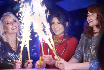 Happy woman holding burning sparklers