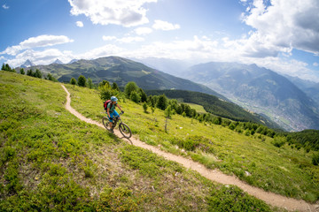 A young woman riding her mountain bike above the Aosta valley, Italy.