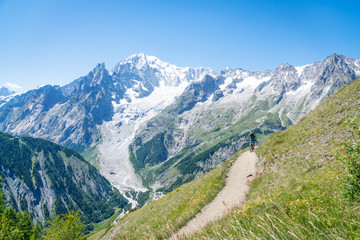 A mountain biker riding on an alpine trail in the Aosta Valley, Italy.