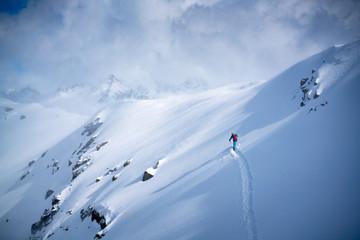 A male skier does off-piste skiing in fresh powder snow in the Sportgastein ski area in Austria.