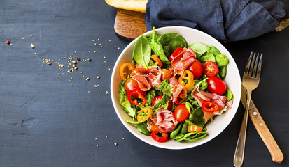 Fresh prosciutto ham and vegetables salad with spinach , tomatoes , peppers and ham seasoned with...