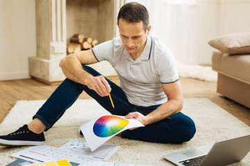 Concentrated designer. Smart serious responsible designer sitting on the floor with a bright color palette while working at his new interesting project