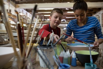 Female potter and boy painting bowl