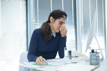 Tired female executive sitting at desk