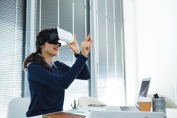 Female executive using virtual headset at desk