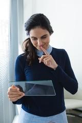 Female executive using glass digital tablet