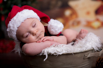 Little baby boy with christmas clothes, sleeping in basket