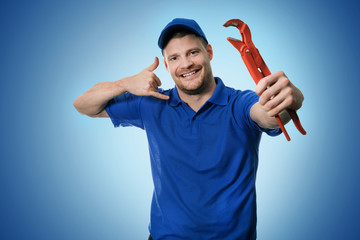 plumbing services - plumber with wrench showing phone call gesture on blue background