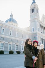 Asian women taking selfie on street