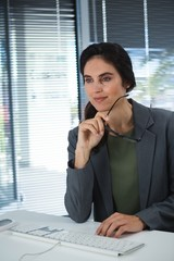 Thoughtful female executive sitting at desk