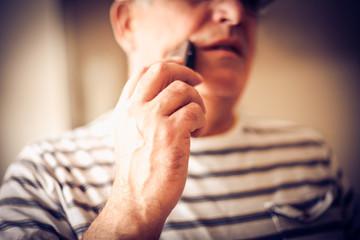 Senior man shaving. Focus on hand.