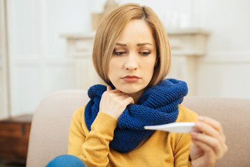 Having a cold. Attractive sad young blond woman feeling down in the mouth and holding a thermometer and having a blue warm scarf on while sitting on the sofa