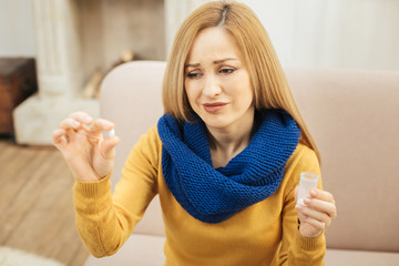 Yuck. Sick young blond long-haired woman wearing a scarf jeans and sweater and sitting on the couch while holding a pill and looking at it with disgust