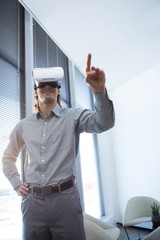 Male executive gesturing while using virtual reality headset