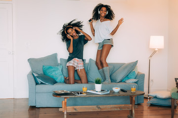 Happy young two black women sitting and standing up in the couch on the computer and mobile phone with headphones dancing .
