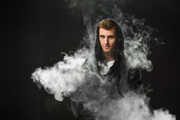 Young bearded man vaping electronic cigarette surrounded by clouds of steam