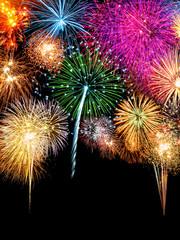 Buntes Silvester Feuerwerk vor schwarzem Hintergrund im Hochformat