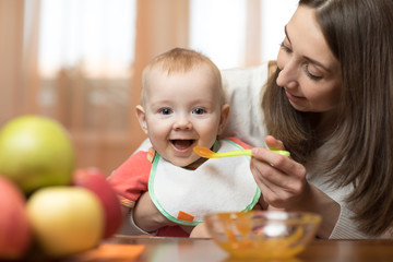 Baby eating healthy food with mother help at home