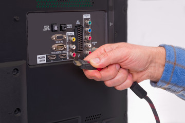 Hand holding HDMI cable in the back of an HDTV box.