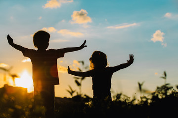 little boy and girl silhouettes play in sunset
