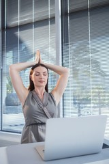 Female executive performing yoga at desk