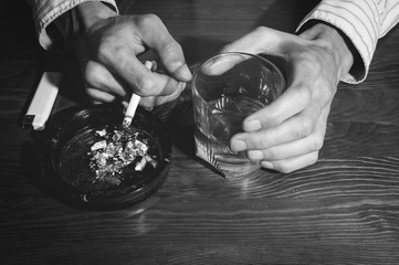 Hands of alcoholic man holding a glass with alcohol drink with smoking cigarette in the ashtray black and white