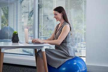 Female executive sitting on exercise ball while using laptop at
