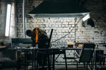Worker cutting metal in dark workshop, sparks fly, industrial work with steel