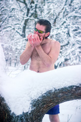 Naked man with sunglasses in the winter forest eating snow