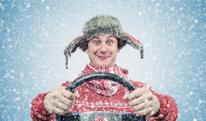 Happy man in red sweater and hat with a steering wheel, snow blizzard. Concept car driver