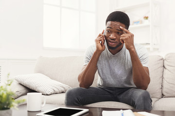 Upset young man talking on mobile at home