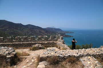 Cefalu, Sicily, Italy. A tourist among the ruins of a medieval fortress on the rock of La Rocca takes picturesque scenery