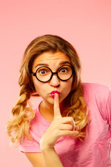 Young funny pretty woman saying shh gesture over pink background.