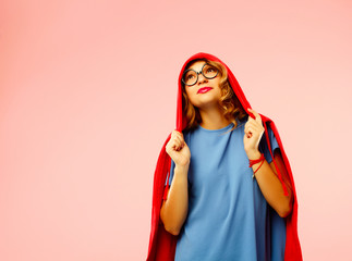 Portrait of young student in black glasses in hood over pink background