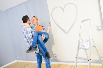 cheerful young love couple in new house painting decorating home and drawing a heart shape on the wall