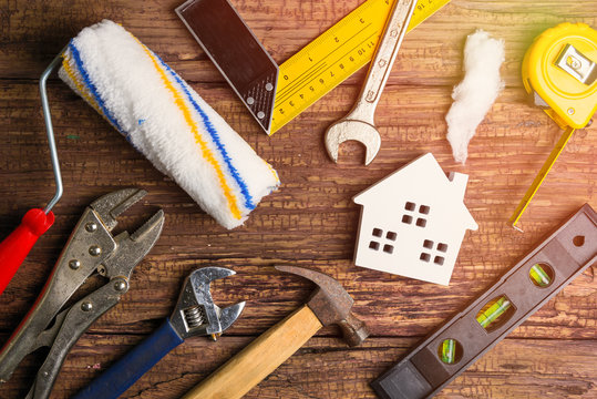 Wooden white house toy and construction tools on wooden background with copy space.Real estate concept, New house concept, Finance loan business concept, Repair maintenance concept.