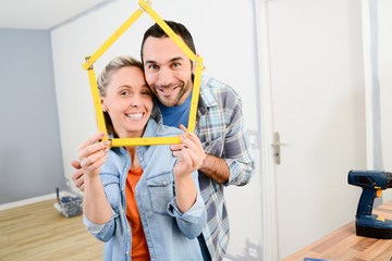 cheerful young couple making future project and renovating new home