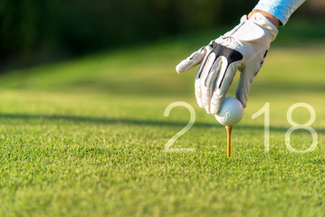 Golfer asian woman putting golf ball for Happy New Year 2018 on the green golf, copy space.   Healthy and Holiday Concept..