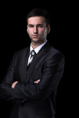 Portrait of a handsome business man  isolated on black.
