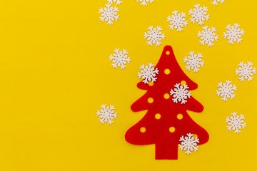 CHRISTMAS TREE WITH SNOE FLAKE ON YELLOW PAPER BACKGROUND FESTIVE IDEAS CONCEPT