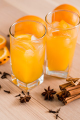 Fresh orange juice in the glass jar. Spices of cinnamon, cardamom, cloves. On a wooden background