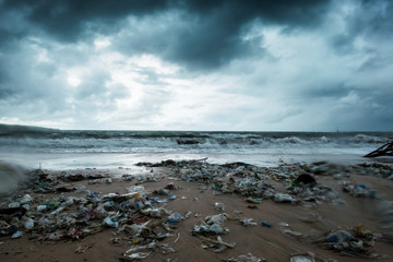 Garbage on beach, environmental pollution in Bali Indonesia. Storm is coming on background. And drops of water are on camera lens. Dramatic view Fotobehang