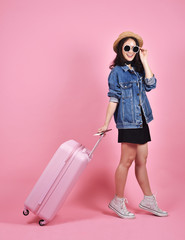 Young woman traveler holding pink suitcase and passport document over pink background, Journey and travel concept.