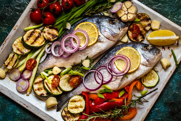 Dorada fish with vegetables, lemon, spices and greens on a blue background